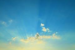 Cielo azul con las nubes y los rayos del sol Fotos de archivo