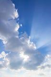 cielo azul con los rayos de la luz que brillan abajo de minúsculo mullido blanco del paso Fotos de archivo