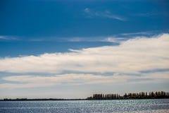 Cielo azul con nubes y un río Foto de archivo