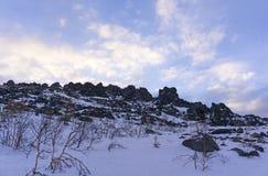 Cielo azul de la mañana sobre el canto de la roca en las montañas del invierno Fotos de archivo libres de regalías