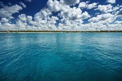 Cielo azul de las nubes mullidas blancas sobre una superficie del mar Imagen de archivo libre de regalías