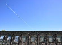 Cielo azul de las ventanas de las fábricas y un avión foto de archivo libre de regalías