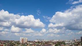 Cielo azul de Timelapse con las nubes de cúmulo blancas sobre la ciudad
