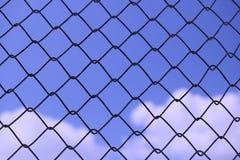 Cielo azul detrás de la reja del alambre - fondo abstracto imágenes de archivo libres de regalías