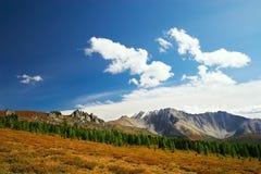 Cielo azul, nubes y montañas. Foto de archivo