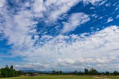 cielo azul nublado con el campo de hierba y las montañas distantes Foto de archivo libre de regalías