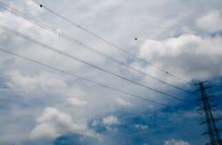 Cielo azul nublado con los pilones de la electricidad Fotografía de archivo libre de regalías
