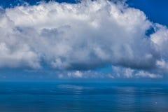 Cielo azul nublado sobre una superficie azul Imágenes de archivo libres de regalías