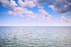 Cielo azul nublado sobre una superficie del mar Imagenes de archivo