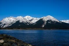 Cielo azul perfecto y agua azul con las montañas de Alaska capsuladas nieve majestuosa. Imagen de archivo