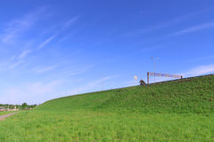 Cielo azul puro, césped verde claro y camino en la colina Foto de archivo