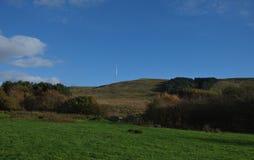 Cielo azul que mira sobre el campo, hierba verde en el lado de la colina, nubes mínimas, foto admitida el Reino Unido fotos de archivo
