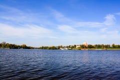 Cielo azul, río y ciudad en la orilla imagenes de archivo