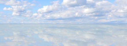 Cielo azul reflejado en horizonte de la orilla del lago Fotos de archivo