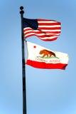 Cielo azul retroiluminado de las banderas de Estados Unidos y de California Imagen de archivo libre de regalías