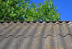 Cielo azul sobre las tejas de tejado viejas del amianto peligroso capaces de utilizar como fondo texturizado Fotografía de archivo