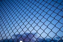 Cielo azul a través de la cerca de la malla de alambre Empañe el fondo, cierre encima de la vista de la jaula del vínculo, papel  Fotografía de archivo