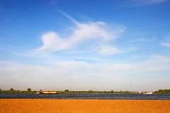 Cielo azul y arena amarilla. Imagen de archivo
