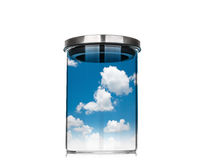 Cielo azul y nube dentro de un tarro de cristal en el fondo blanco Imagenes de archivo
