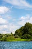 Cielo azul y nubes blancas, bosque verde y aguas azules del río Imagen de archivo libre de regalías