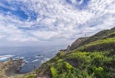 Cielo azul y playa con la roca del verdor Imagen de archivo libre de regalías