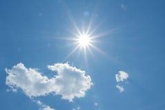 Cielo blu con le nuvole ed i raggi di sole lanuginosi Fotografia Stock