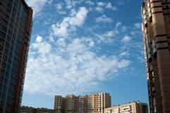 Cielo blu con le piccole nuvole fra le case Fotografie Stock Libere da Diritti