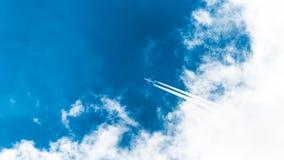 Cielo blu in cui il piano vola, volante dalle nuvole Bella vista fotografia stock libera da diritti