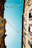 Cielo blu e bandiere fra le case fotografia stock