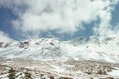 Cielo blu e montagne innevate bianche e del nuvola Immagine Stock