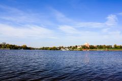 Cielo blu, fiume e città sulla riva immagini stock