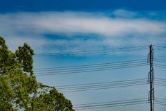 Cielo blu il giorno soleggiato con il palo ad alta tensione dell'alimentazione Fotografia Stock Libera da Diritti