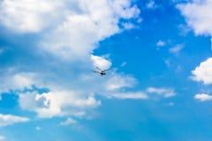 Cielo blu luminoso con le nuvole e l'elicottero volante immagini stock libere da diritti