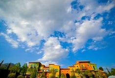 Cielo blu nuvoloso con il piccolo villaggio d'annata immagini stock