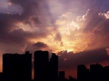Cielo blu nuvoloso pazzo con la disposizione della siluetta leggera contro la scena urbana della città fotografia stock libera da diritti