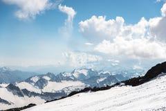 Cielo blu scuro con le nuvole sui picchi rocciosi delle montagne coperte di ghiacciai e di neve Fotografia Stock