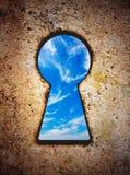 Cielo in buco della serratura sulla vecchia parete Immagine Stock Libera da Diritti