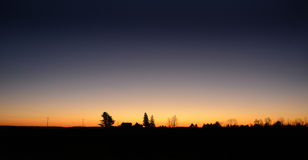 Cielo claro con paisaje silueteado puesta del sol anaranjada Fotografía de archivo libre de regalías