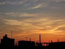 Cielo coloreado de la puesta del sol sobre siluetas industriales oscuras imagen de archivo