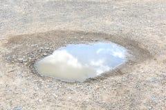 Cielo con la reflexión de las nubes en charco del agua Imagenes de archivo
