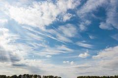 Cielo con las nubes del cúmulo y de cirro y la estela de vapor Imagen de archivo