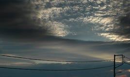 Cielo con las nubes y los alambres blancos de la electricidad Imagen de archivo