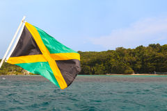 Cielo de la playa del mar de la bandera de Jamaica que agita Imágenes de archivo libres de regalías