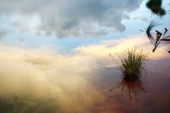 Cielo de la puesta del sol de la reflexión con la nube en el agua del verano del lago con meado Fotos de archivo libres de regalías