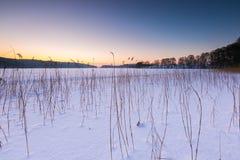 Cielo de la puesta del sol sobre el lago congelado y nevoso Foto de archivo