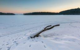 Cielo de la puesta del sol sobre el lago congelado y nevoso Imagen de archivo
