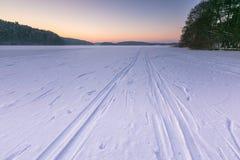 Cielo de la puesta del sol sobre el lago congelado y nevoso Fotos de archivo libres de regalías