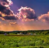 Cielo de la puesta del sol sobre una granja de la granja imagen de archivo