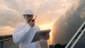 Cielo de la puesta del sol y una situación equipada del especialista de la energética cerca de un panel solar almacen de metraje de vídeo
