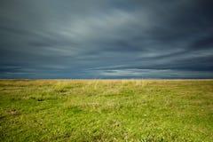 Cielo de la tormenta sobre campo verde Foto de archivo libre de regalías